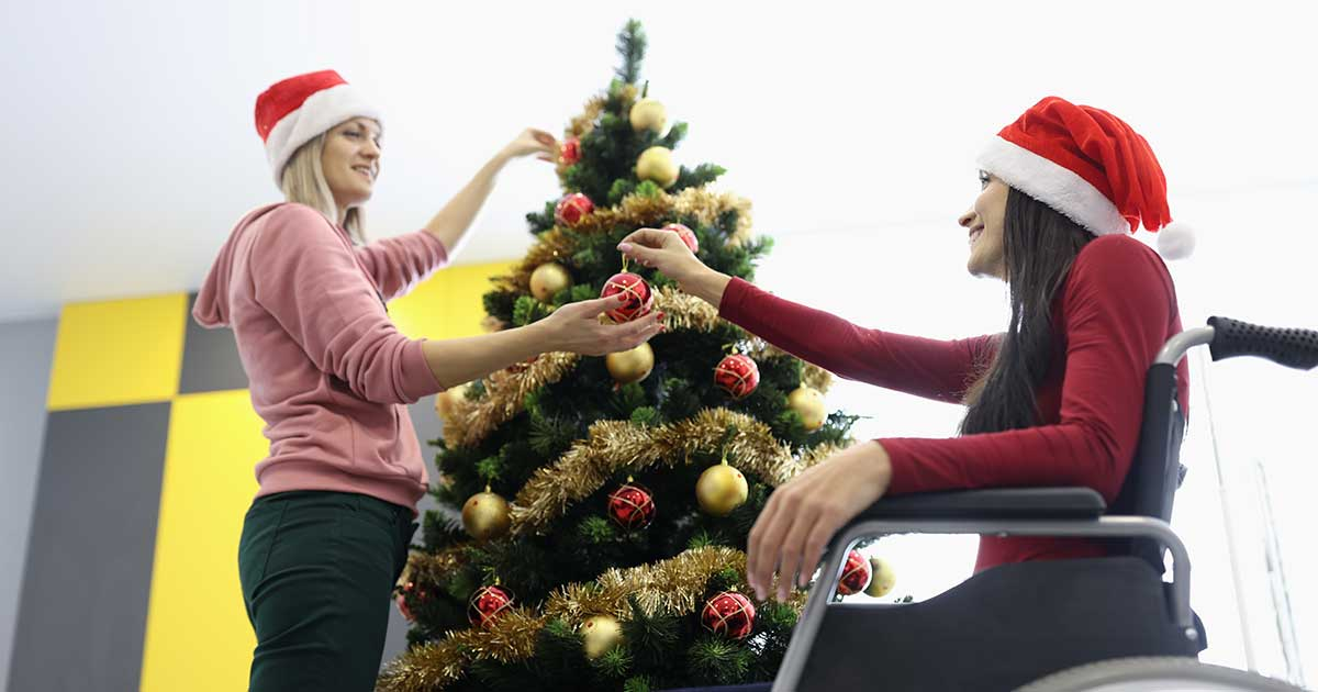 Woman in wheelchair and santa hat with her carer decorating christmas tree at home.