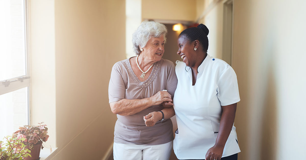 Portrait of happy female Support Worker and senior woman walking together at home.